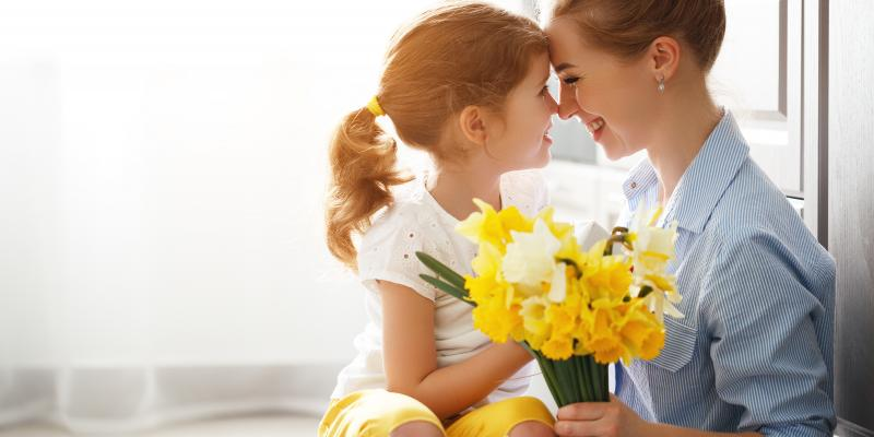 young girl and her mom holding yellow flowers