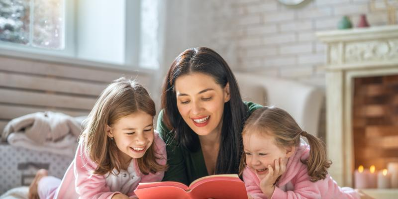 mother reading to her two daughters