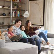 family laughing on couch flipping through tv channels