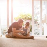 dad sitting on floor with daughter on tablet