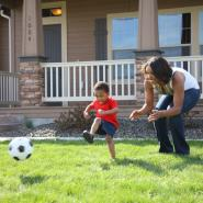 mom and son playing soccer on front lawn